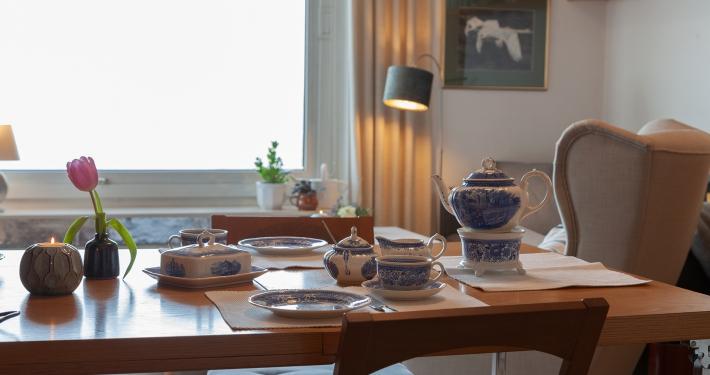 Speisen Sie mit dem schönen blau weißen Tischservice und genießen Sie dabei den herrlichen Ausblick aus dem großen Fenster der Ferienwohnung Fiedler.
