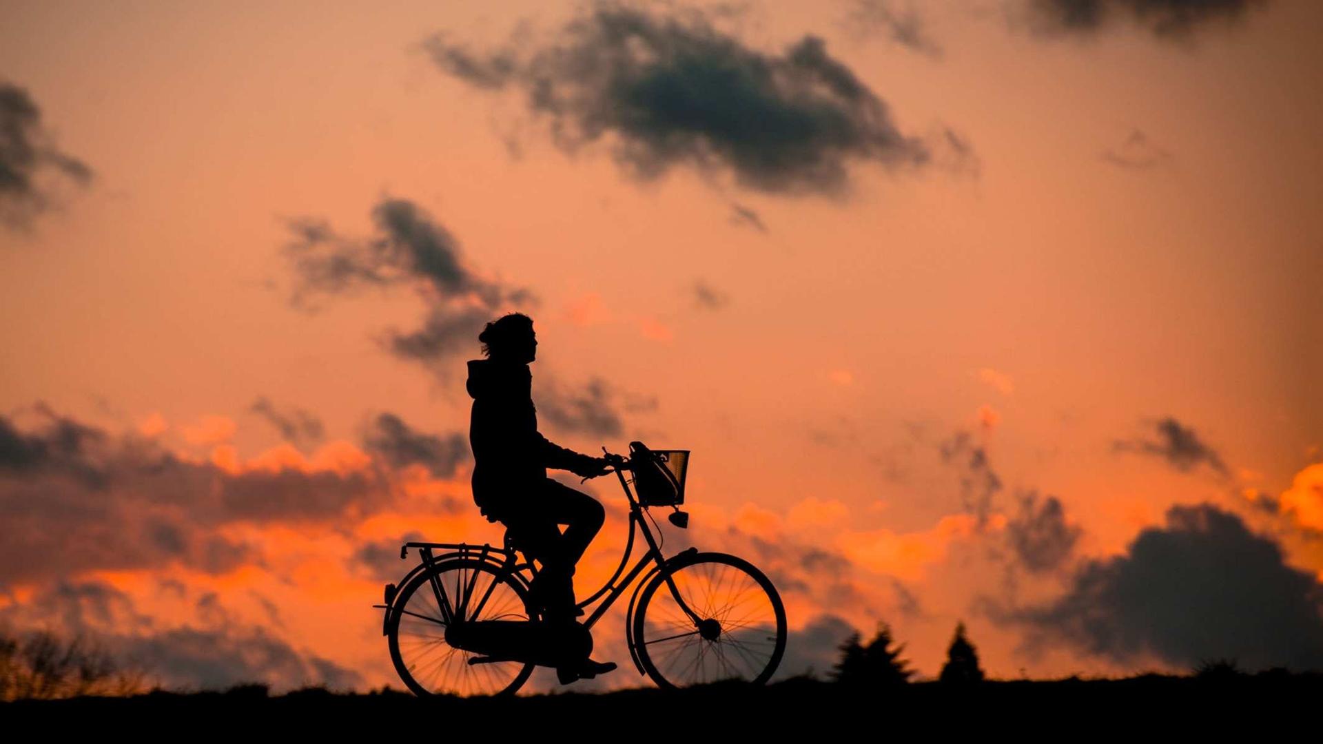 Ein Fahrradfahrer in den Abendstunden radelt durch die Gegend.