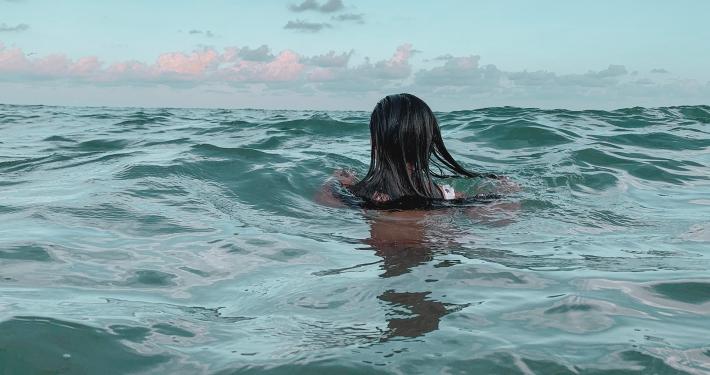 Eine junge Frau schwimmt im Meer.