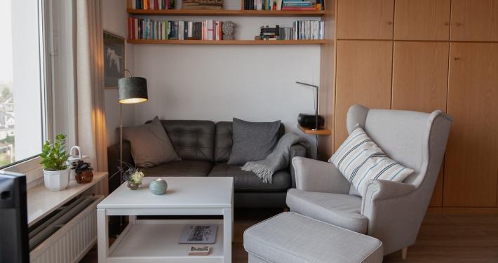 Der Wohnbereich der Ferienwohnung Fiedler mit seinem Zweier-Sofa und dem gemütlichen Ohrensessel mit Hocker dazu.