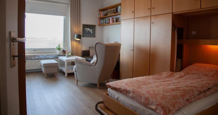 Ein Blick aus dem Flur in das erste Zimmer der Ferienwohnung Fiedler mit dem ausgeklappten Bett und der Wohnecke im Hintergrund.